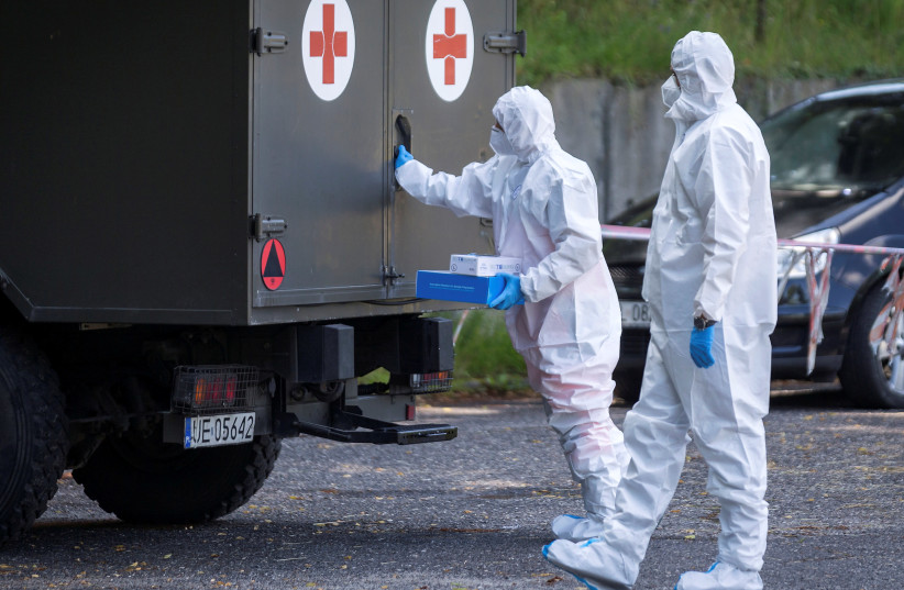 Health workers wearing protective gear are seen at a mobile testing station for miners of the Bielszowice coal mine, following the coronavirus disease (COVID-19) outbreak in Ruda Slaska, Poland July 27, 2020. (photo credit: REUTERS)