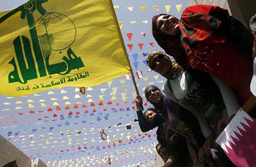 Les résidents tiennent les drapeaux du Hezbollah et du Qatar lors de la visite de l'émir du Qatar, Cheikh Hamad bin Khalifa al-Thani, au village de Bint Jbeil, dans le sud du Liban, le 31 juillet 2010. (Crédit photo: REUTERS)