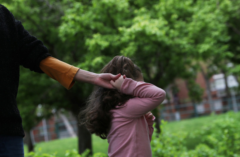 Susana Cristo Anzola is pulled by her daughter Olivia, a 4-year-old on the autism spectrum, to enter a closed playground during the lockdown amid the coronavirus disease (COVID-19) outbreak in Madrid, Spain, April 9, 2020. (photo credit: REUTERS/SUSANA VERA)