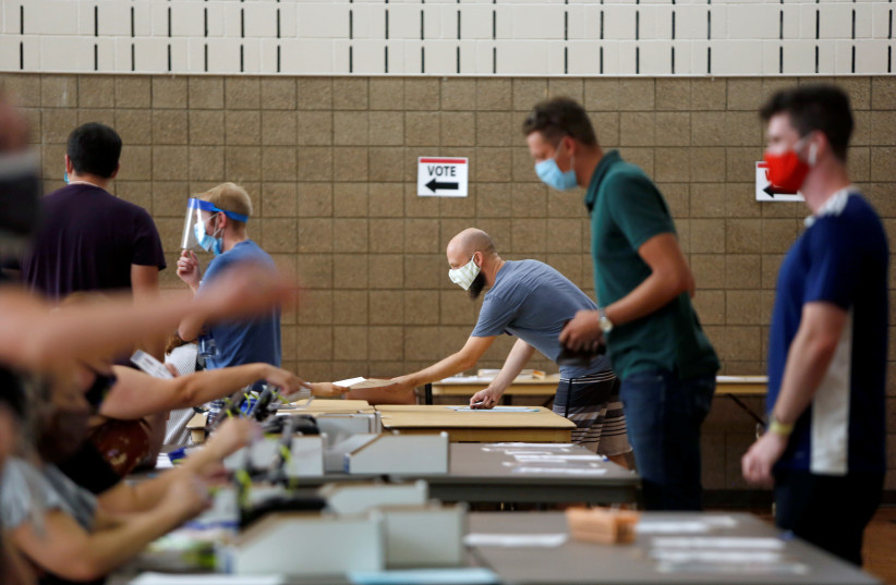 Voters check in at Whittier Community Center during the primary election in Minneapolis, Minnesota, U.S. August 11, 2020. (photo credit: REUTERS/NICOLE NERI)