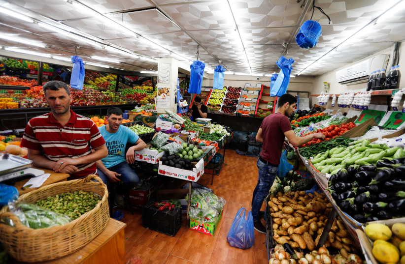 Palestinians buy vegetables and fruits at a shop during the holy month of Ramadan, in the West Bank city of Hebron,  May 16, 2019.  (photo credit: WISAM HASHLAMOUN/FLASH90)