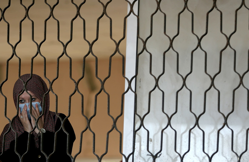 A Palestinian woman waits before leaving Rafah border crossing with Egypt, which was reopened for the first time since it was closed in March over Covid-19 concerns, in the southern Gaza strip August 11, 2020. (photo credit: IBRAHEEM ABU MUSTAFA / REUTERS)