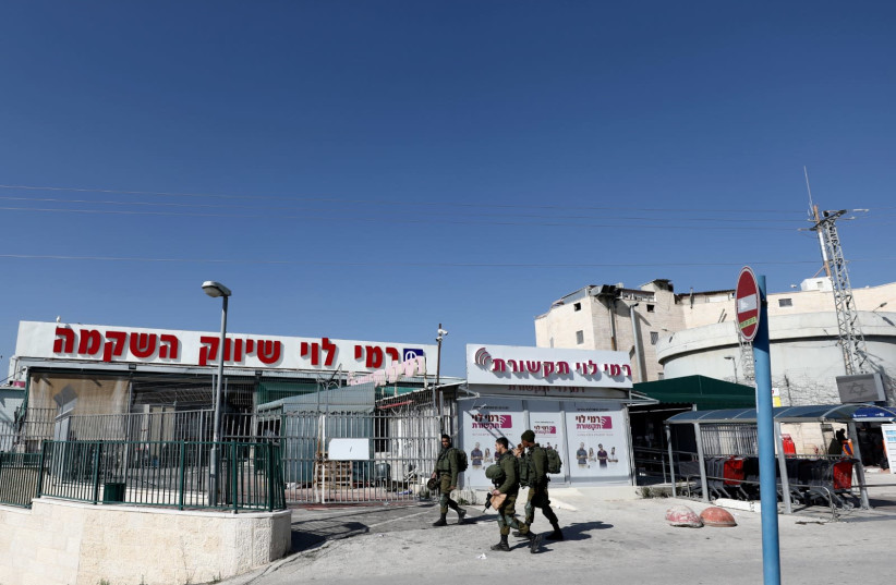 Israeli soldiers walk past Rami Levy chain store in the Israeli Sha'ar Binyamin Industrial Zone in the West Bank (photo credit: REUTERS/AMMAR AWAD)