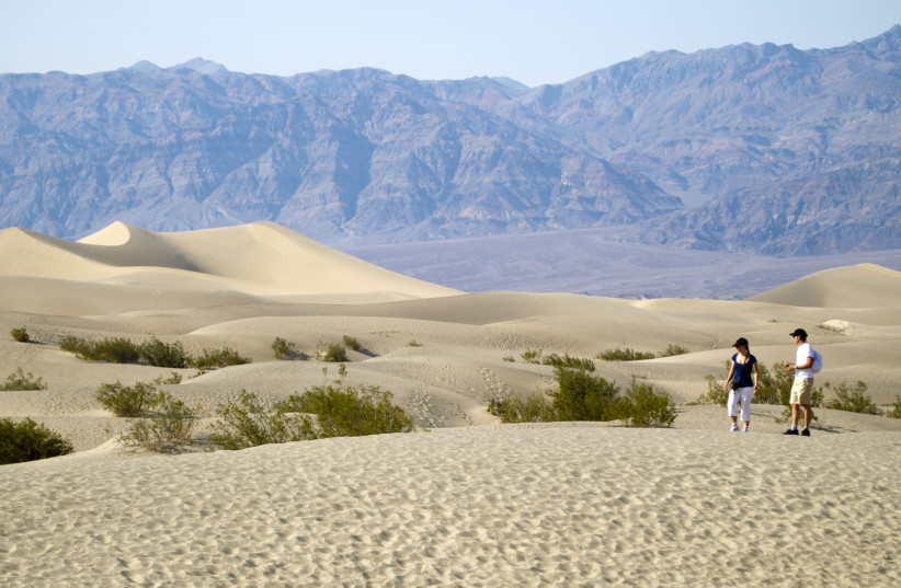 Italian tourists walk in the Mesquite Dunes during heat wave in Death Valley National Park, California (photo credit: STEVE MARCUS/REUTERS)