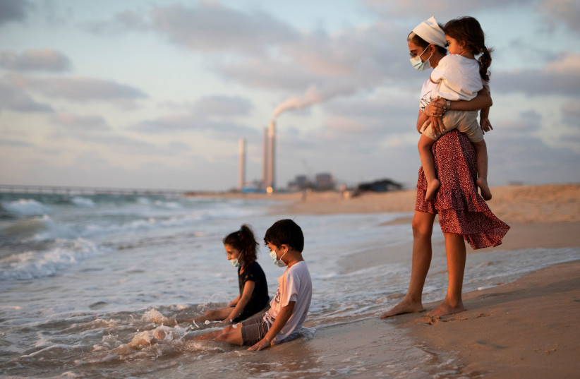 Children wearing masks play in the water along the shore of the Mediterranean Sea as they visit Zikim beach, amid the coronavirus disease (COVID-19) outbreak, in southern Israel July 21, 2020 (photo credit: REUTERS/AMIR COHEN)