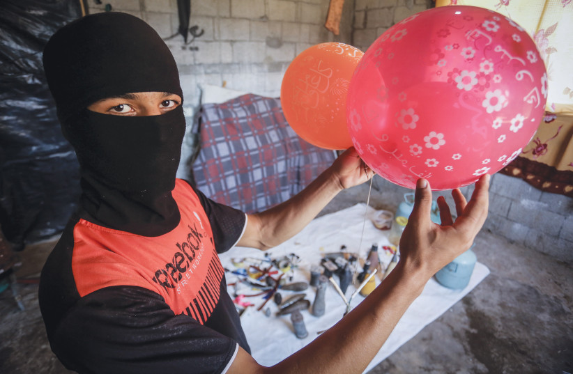 PALESTINIANS IN Rafah earlier this month prepare balloons attached with flammable materials to be released into Israel. (photo credit: ABED RAHIM KHATIB/FLASH90)
