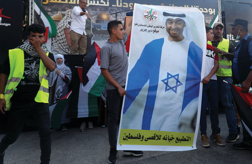 PALESTINIANS HOLD a picture depicting Abu Dhabi Crown Prince Mohammed bin Zayed al-Nahyan wearing a Jewish star during a protest against the UAE normalizing relations with Israel, in Turmus Aiya near Ramallah, on Wednesday. (photo credit: MOHAMAD TOROKMAN/REUTERS)