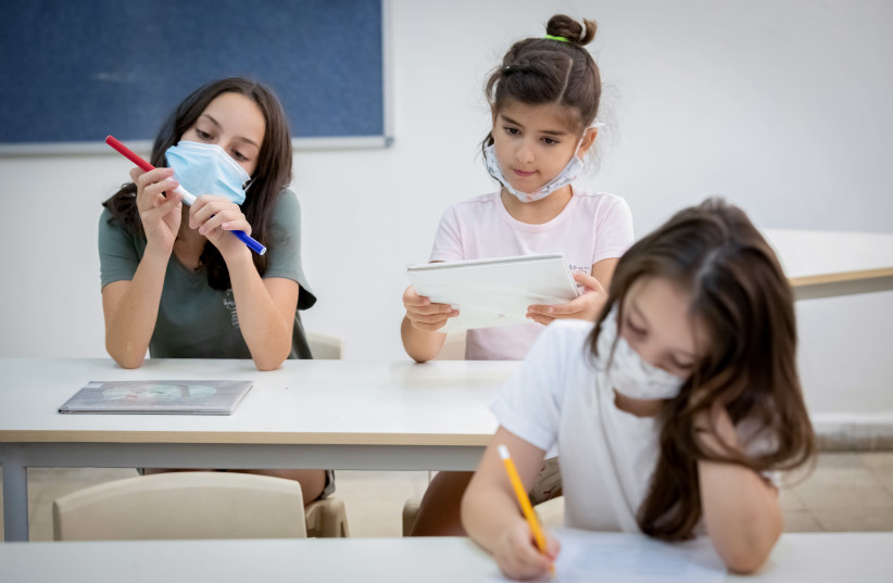 Israeli students wearing protective face masks in order to prevent the spread of the coronavirus in a school in Tel Aviv, August 23, 2020 (photo credit: CHEN LEOPOLD/FLASH90)