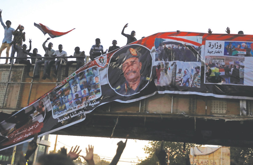 Protestors tear down a picture of Lt.-Gen. Abdel Fattah Al-Burhan Abdelrahman minutes after it was hung on a bridge in Khartoum, Sudan, in April 2019. (photo credit: UMIT BEKTAS / REUTERS)