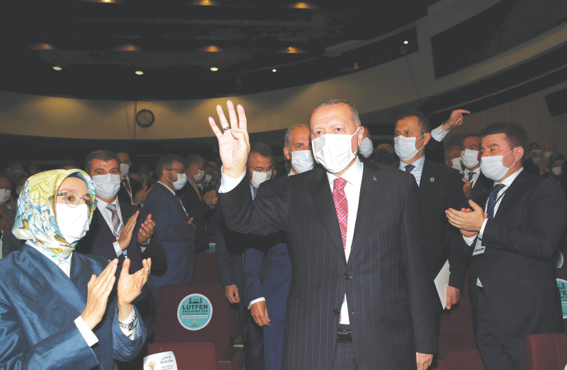 Turkish President Tayyip Erdogan wears a protective mask while greeting members of his party in Ankara on August 13, 2020 (photo credit: REUTERS)