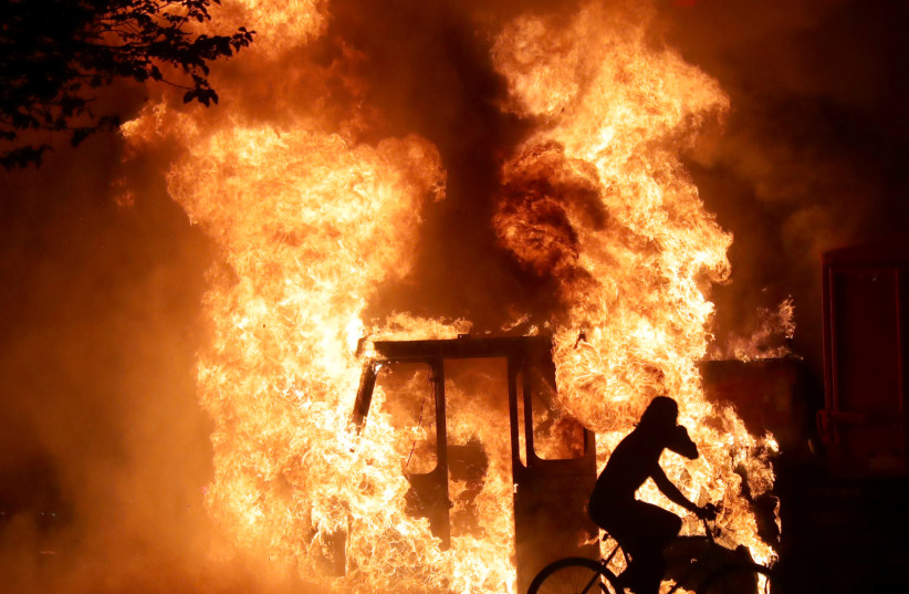 A man on a bike rides past a city truck on fire outside the Kenosha County Courthouse in Kenosha, Wisconsin, U.S., during protests following the police shooting of Black man Jacob Blake August 23, 2020. (photo credit: MIKE DE SISTI/MILWAUKEE JOURNAL SENTINEL VIA USA TODAY VIA REUTERS)