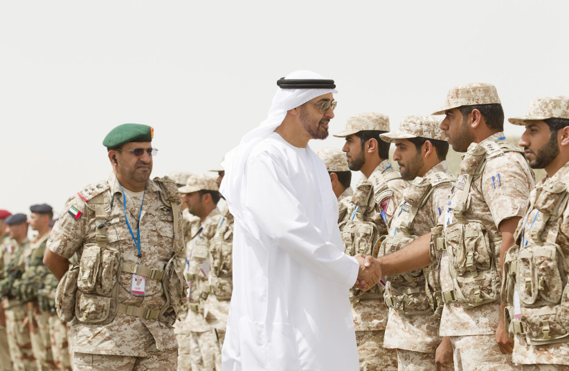 Abu Dhabi Crown Prince Sheikh Mohammed Bin Zayed Al Nahyan shakes hands with a member of the UAE armed forces during joint military manoeuvres between the UAE and the French army in the desert of Abu Dhabi May 2, 2012 (photo credit: REUTERS/WAM/HANDOUT)