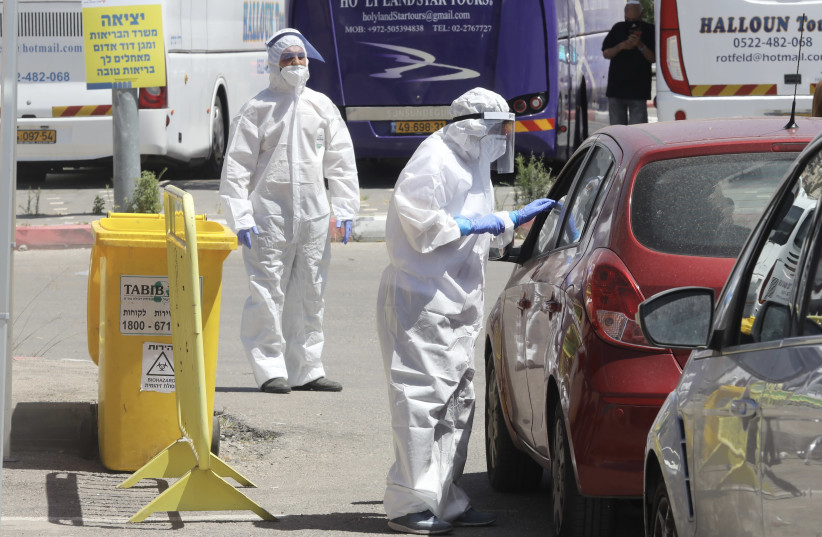 Inspectors conduct coronavirus tests at a checkpoint in Jerusalem (photo credit: MARC ISRAEL SELLEM)
