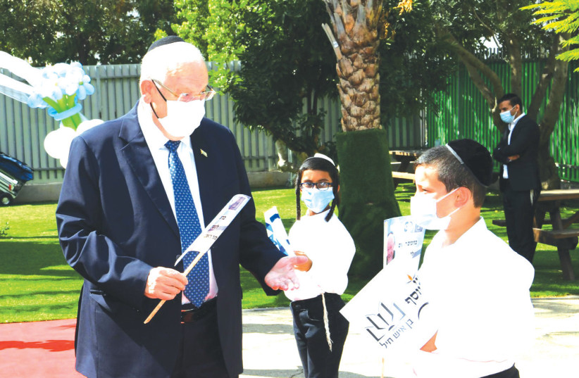 President Reuven Rivlin is greeted by students of Ben Ish Hayil Talmud Torah and Yeshivot in Rehovot, August 2020 (photo credit: AMOS BEN GERSHOM, GPO)