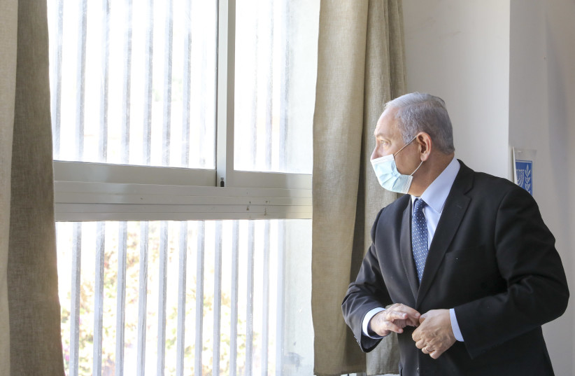 Prime Minister Benjamin Netanyahu looking out a barred window (photo credit: MARC ISRAEL SELLEM)