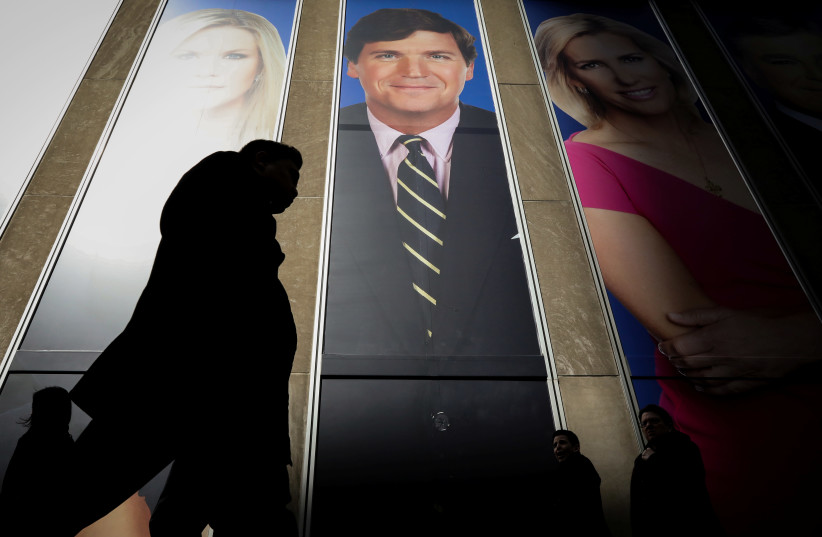 People pass by a promo of Fox News host Tucker Carlson on the News Corporation building in New York, U.S., March 13, 2019 (photo credit: REUTERS/BRENDAN MCDERMID)
