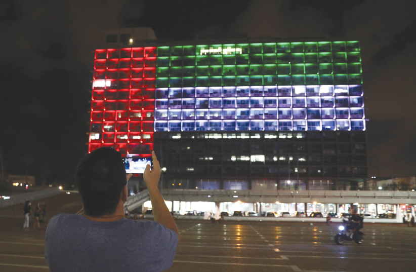 A MAN takes a picture as Tel Aviv City Hall is lit in the image of the United Arab Emirates national flag, following the announcement of a deal to normalize relations. (photo credit: AMMAR AWAD/REUTERS)