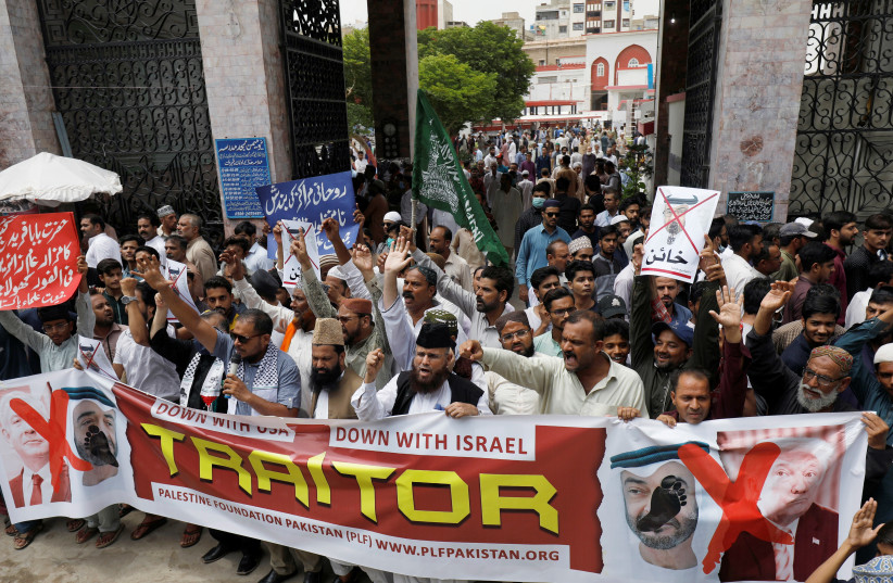 Supporters of the Palestine Foundation Pakistan (PLF) chant slogans as they carry a banner in support of Palestinian people to condemn the diplomatic agreement between the United Arab Emirates (UAE) and Israel, during a protest in Karachi, Pakistan August 21, 2020 (photo credit: REUTERS/AKHTAR SOOMRO)