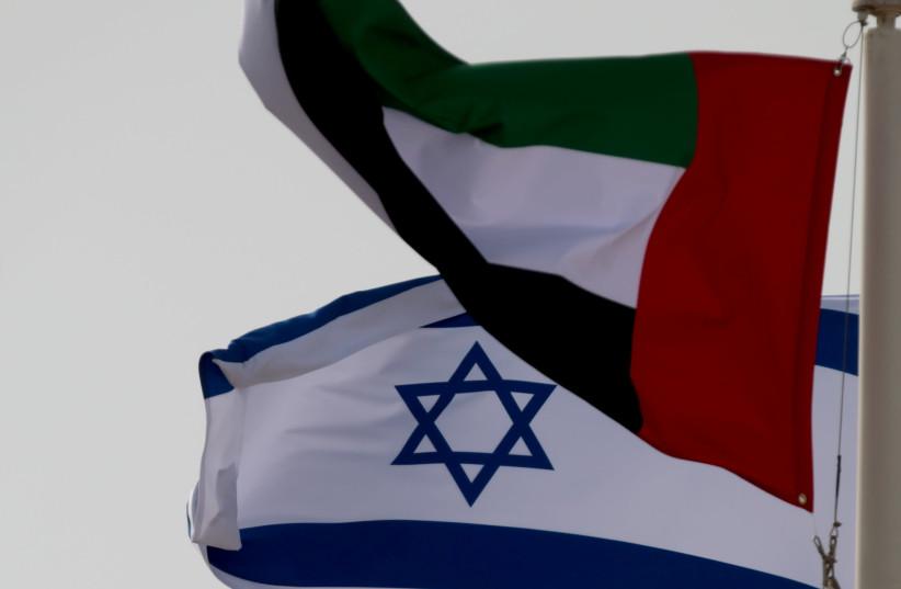 A United Arab Emirates (UAE) flag waves alongside an Israeli flag (photo credit: REUTERS/CHRISTOPHER PIKE)