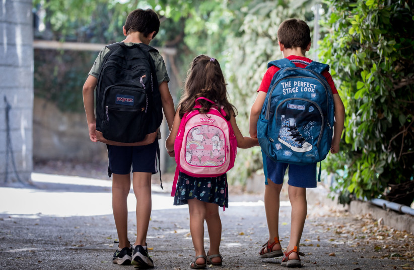 Israeli kids wearing school bags ahead of the first day of school and kindergarten outside their home in Jerusalem on August 31, 2020, The Israeli secular state education system will open tomorrow.  (photo credit: YONATAN SINDEL/FLASH90)