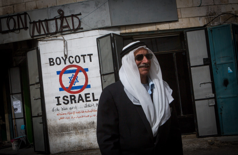 A Palestinian man walks by a grafitti sign calling to boycott Israel seen on a street in the West Bank city of Bethlehem on February 11, 2015. (photo credit: MIRIAM ALSTER/FLASH90)