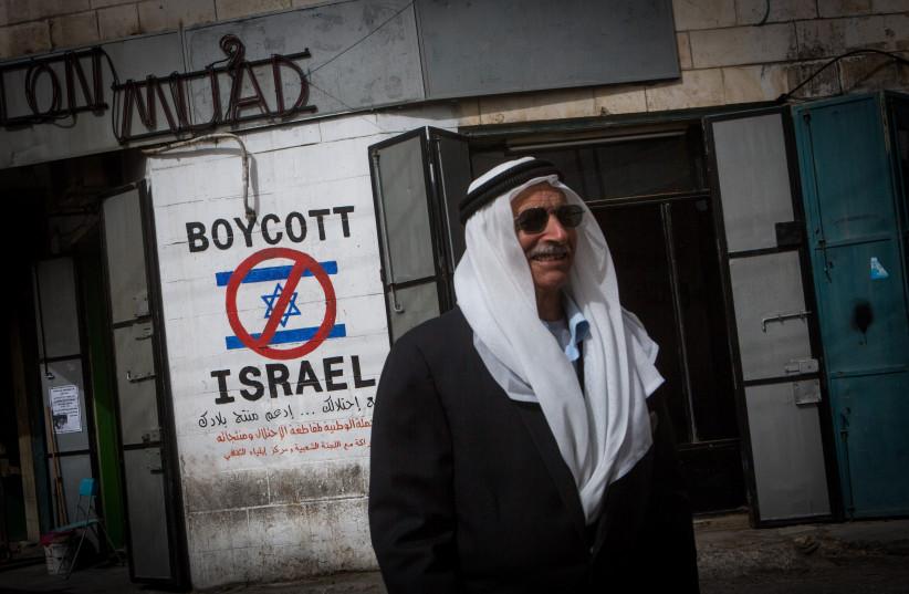 Un Palestinien passe devant un graffiti appelant à boycotter Israël vu dans une rue de Bethléem, en Cisjordanie, le 11 février 2015 (Crédit photo: MIRIAM ALSTER / FLASH90)