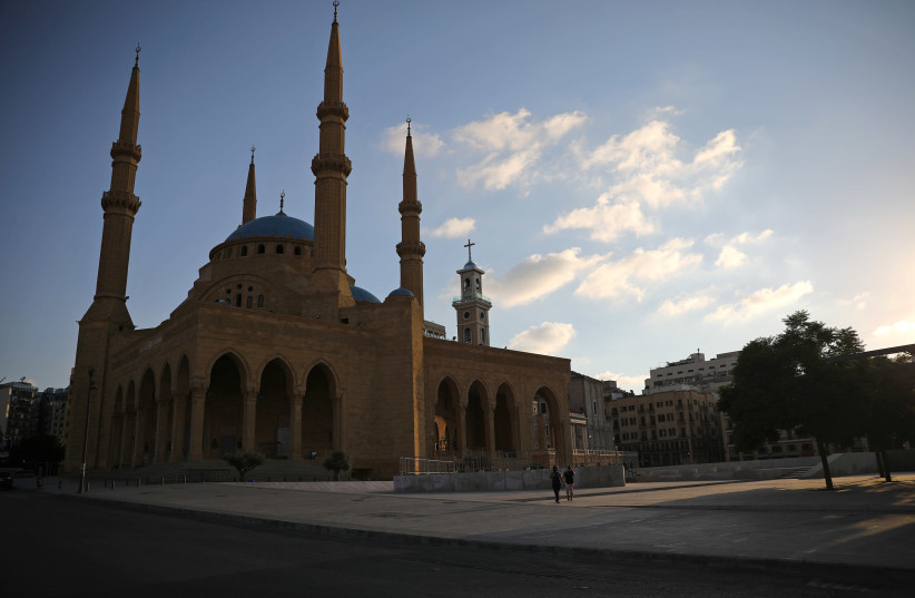 People walk along an empty street near al-Amin mosque, as Lebanon imposed a partial lockdown for two weeks starting on Friday in an effort to counter the spread of the coronavirus disease (COVID-19) which have spiralled since the catastrophic explosion at Beirut port, Lebanon August 21, 2020 (photo credit: REUTERS/ALKIS KONSTANTINIDIS)