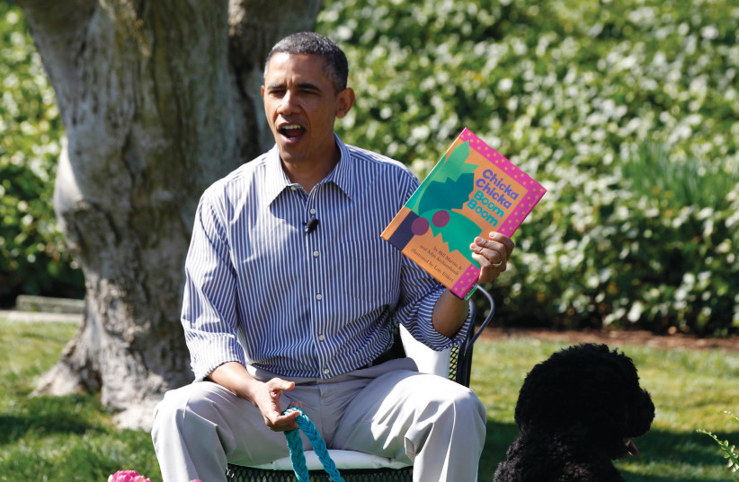 THEN-PRESIDENT Barack Obama reads to children alongside his faithful companion, dog Bo, during the White House Easter Egg Roll in 2013 (photo credit: JASON REED/REUTERS)