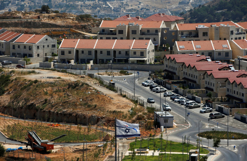 The Israeli national flag flutters as apartments are seen in the background in the Israeli settlement of Efrat in the West Bank August 18, 2020. (photo credit: RONEN ZVULUN/REUTERS)