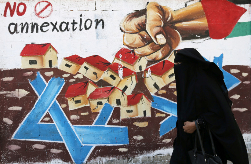 A Palestinian woman walks past a mural against Israel's plan to annex parts of the Israeli-occupied West Bank, in Rafah in the southern Gaza Strip July 14, 2020. (photo credit: IBRAHEEM ABU MUSTAFA/REUTERS)