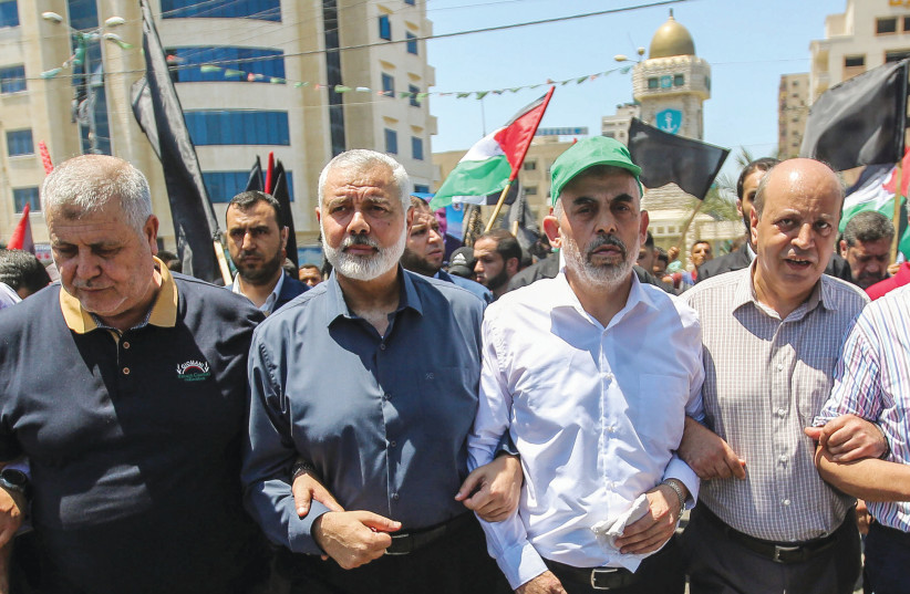 HAMAS LEADERS Ismail Haniyeh and Yahya Sinwar march to protest US President Donald Trump's 'Deal of the Century,' in Gaza City in June 2019. (photo credit: HASSAN JEDI/FLASH90)