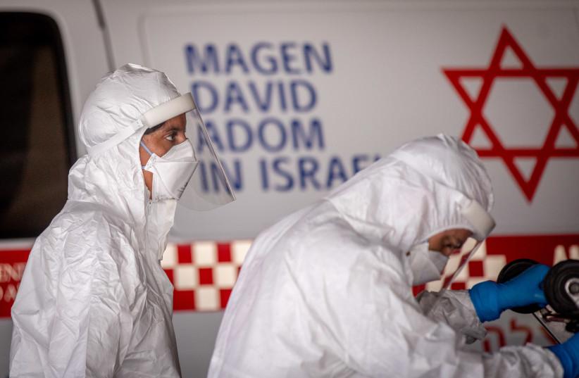 Magen David Adom workers wearing protective clothing seen outside the coronavirus unit at Shaare Zedek Medical Center, Jerusalem, September 6, 2020 (photo credit: YONATAN SINDEL/FLASH90)
