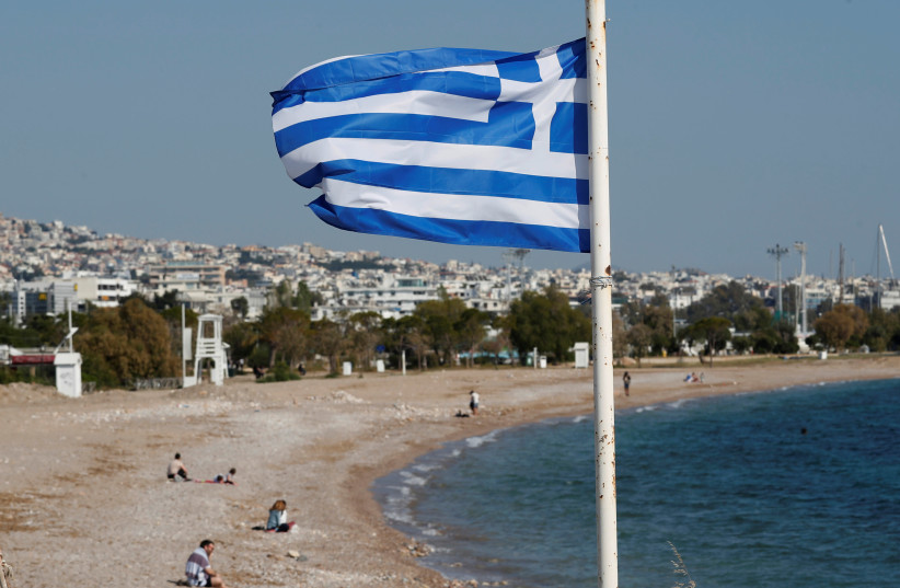 A Greek national flag flutters as people visit a beach, following the coronavirus disease (COVID-19) outbreak, in Athens, Greece, April 28, 2020. (photo credit: GORAN TOMASEVIC/REUTERS)