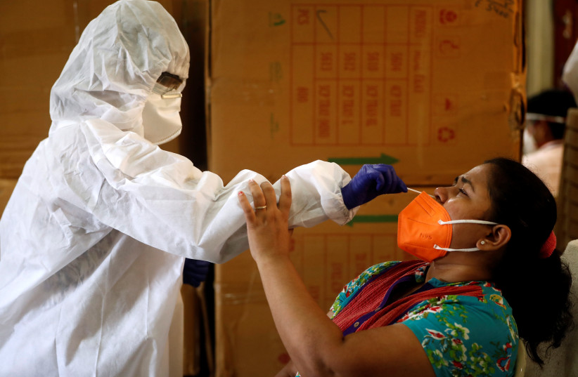 A health worker in personal protective equipment (PPE) collects a swab sample from a woman during a rapid antigen testing campaign for the coronavirus disease (COVID-19) in Mumbai, India, September 7, 2020 (photo credit: REUTERS/FRANCIS MASCARENHAS)