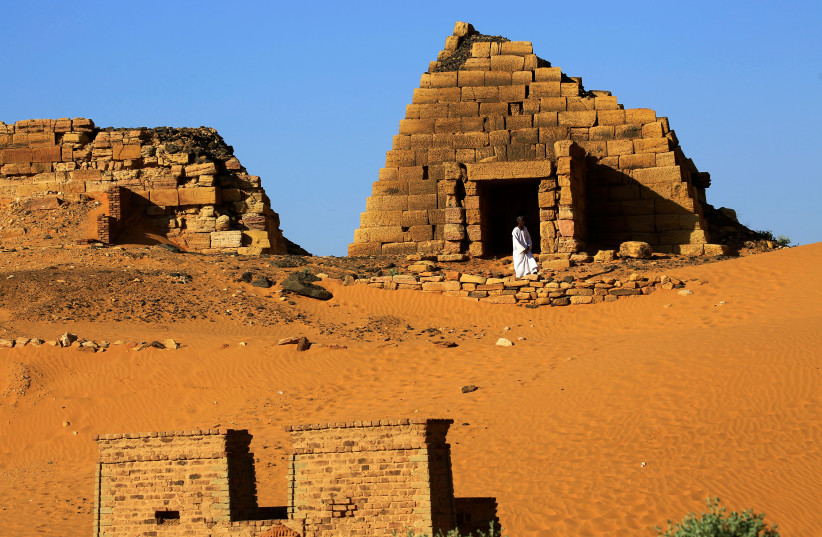Man walks past the Royal Cemeteries of Meroe Pyramids in Begrawiya at River Nile State (photo credit: REUTERS)