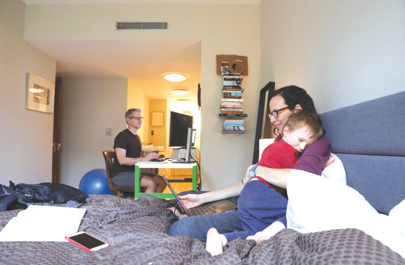 Naomi Hassebroek holds her son Felix while working with her husband, Doug Hassebroek, at their home, in Brooklyn, New York, in March 2020 (photo credit: CAITLIN OCHS/REUTERS)