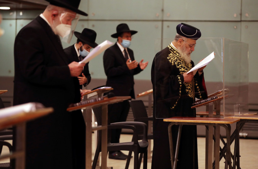 Sephardi Chief Rabbi Yitzhak Yosef (right) leads a prayer for stopping the spread of coronavirus pandemic at the Western Wall on July 21 (photo credit: AMMAR AWAD / REUTERS)