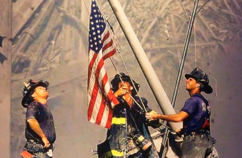 'Raising the Flag at Ground Zero' is a photograph by Thomas E. Franklin of 'The Record' taken on September 11, 2001. The picture shows three New York City firefighters raising the US flag at Ground Zero of the World Trade Center following the 9/11 attacks (photo credit: THOMAS E. FRANKLIN)