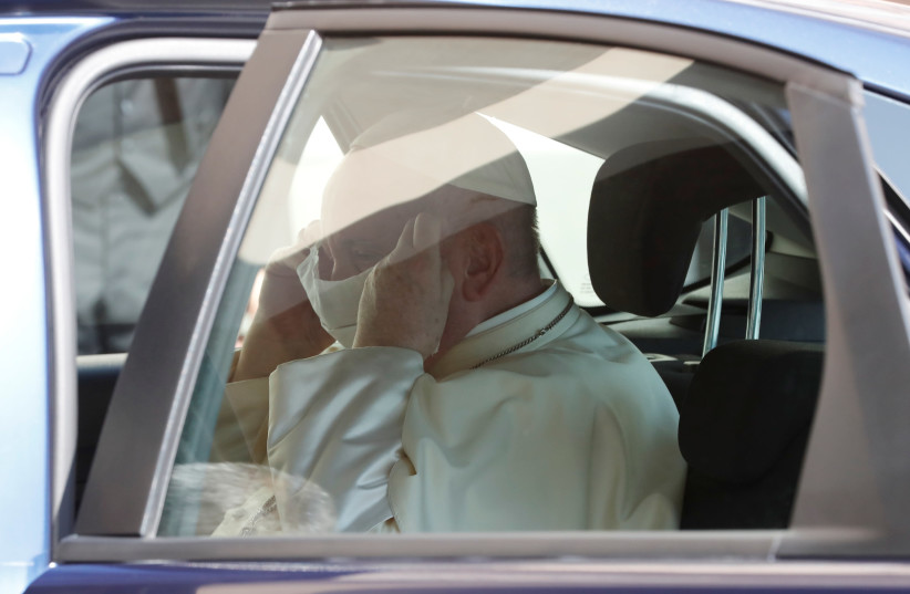 Pope Francis puts on a protective face mask as he enters the car after holding the weekly general audience, at the Vatican September 9, 2020. (photo credit: REMO CASILLI/ REUTERS)