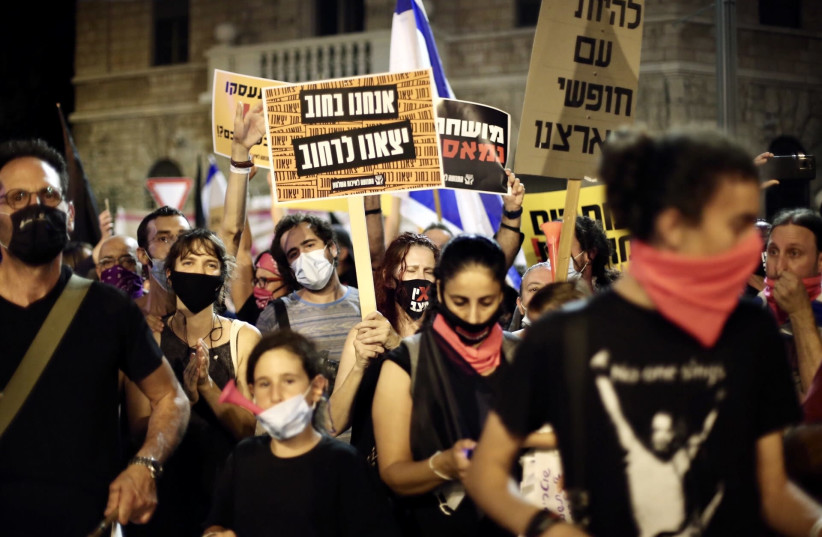 Demonstrators protest the government's mismanagement of the fight against COVID-19 and demand the resignation of Prime Minister Benjamin Netanyahu in front of his Jerusalem residence, Aug. 29, 2020. (photo credit: MOSTAFA ALKHAROUF/ANADOLU AGENCY VIA GETTY IMAGES)
