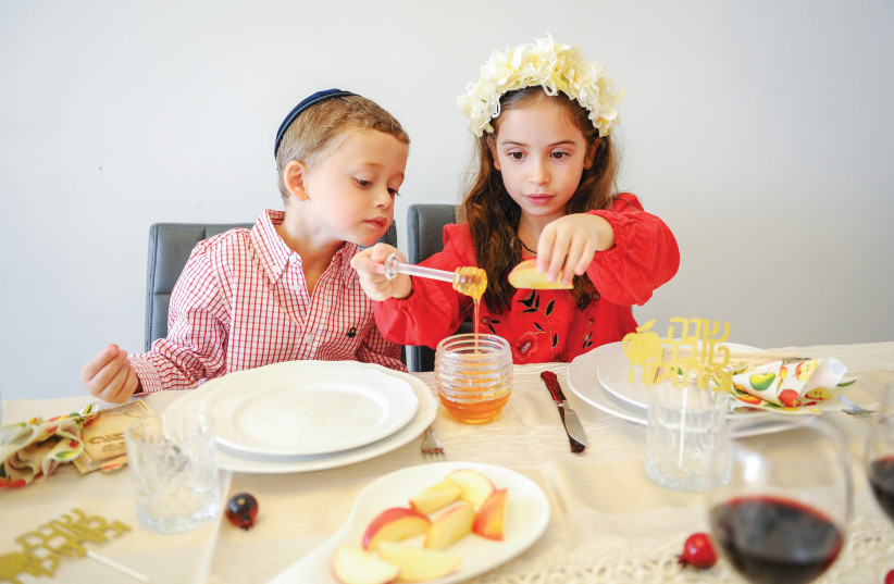 DIPPING APPLES in honey for a sweet new year (photo credit: MENDY HECHTMAN/FLASH90)