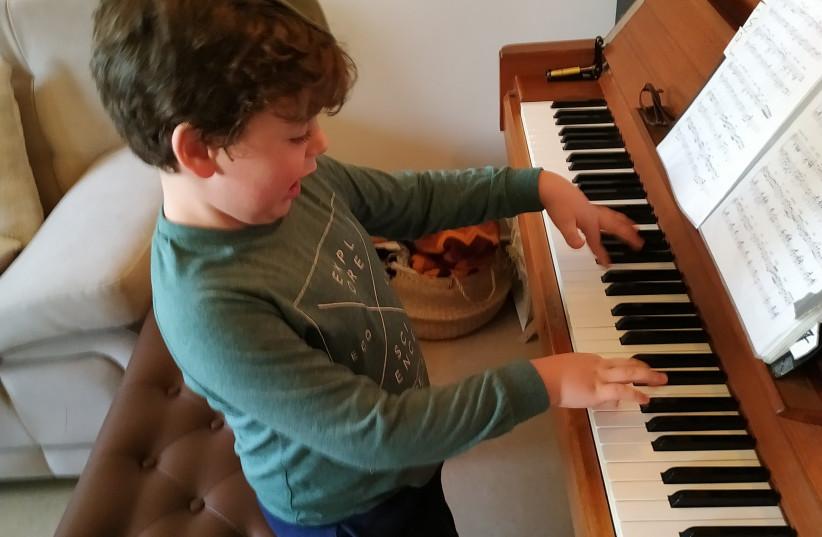 Schertzman's grandson, Eli Schertzman, playing the piano in Efrat (photo credit: Courtesy)