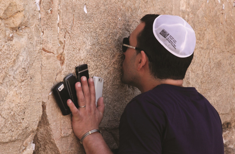 A man holds up his cellphones to the Western Wall (photo credit: MARC ISRAEL SELLEM)