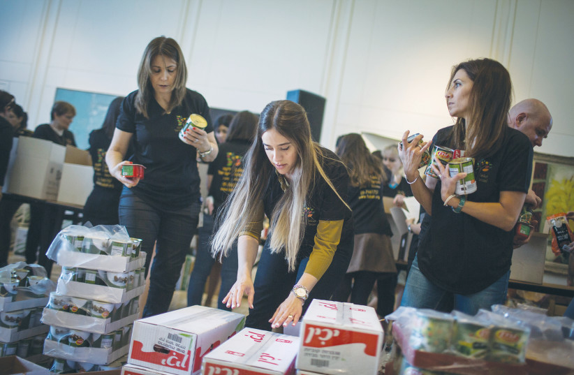 LEKET ISRAEL volunteers and President's Residence workers pack food boxes for families in need, at the President's Residence in Jerusalem in April. (photo credit: HADAS PARUSH/FLASH90)