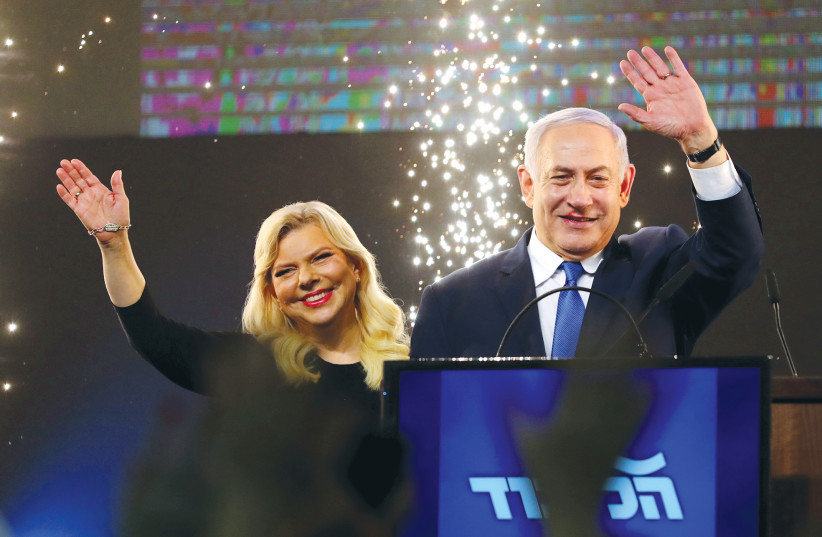 PRIME MINISTER Benjamin Netanyahu stands next to his wife, Sara, after speaking to supporters at his Likud party headquarters in Tel Aviv on March 3. (photo credit: AMIR COHEN/REUTERS)
