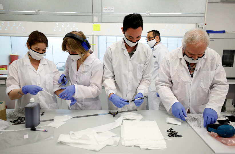 Employees of Israel's Sonovia Ltd, makers of washable and reusable antiviral masks, which the company says can help stop the spread of the coronavirus disease (COVID-19), work at their laboratory in Ramat Gan, Israel May 17, 2020 (photo credit: REUTERS/AMIR COHEN)