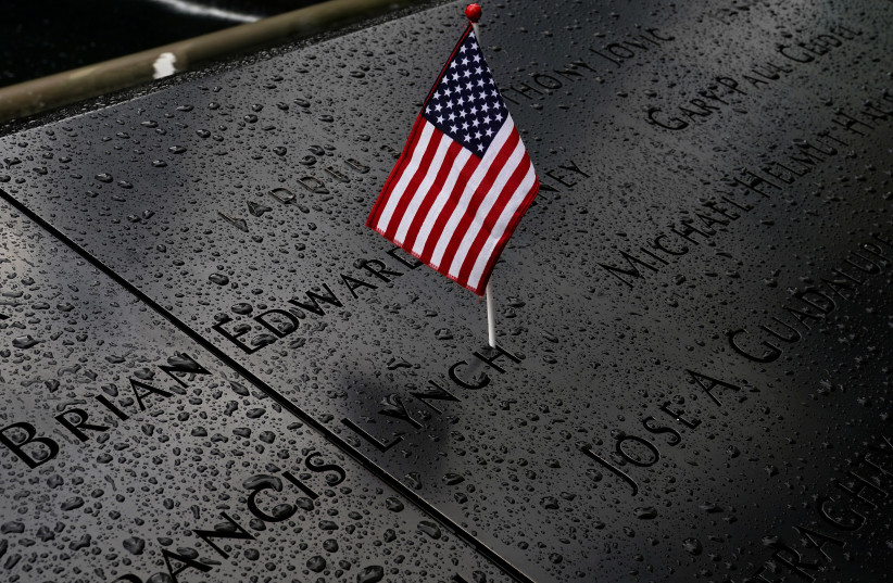 Rain drops rest near a US flag at the south reflecting pool at the National 9/11 Memorial the day before the 19th anniversary of the 9/11 attacks, New York City, September 10, 2020. (photo credit: REUTERS/CARLO ALLEGRI)