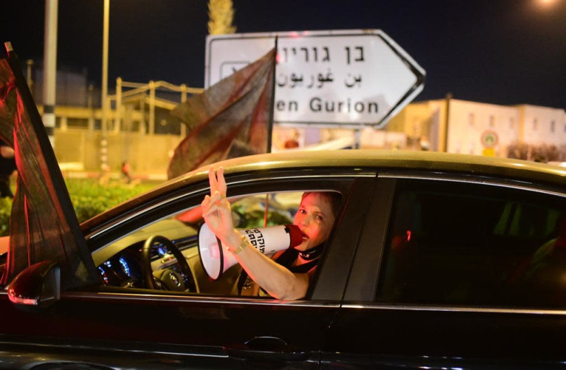 A woman is seen at the anti-Netanyahu protest located Ben-Gurion airport, on the night Prime Minister Benjamin Netanyahu is set to fly to the United States for the signing of the UAE-Bahrain deal. September, 2020.  (photo credit: AVSHALOM SASSONI)