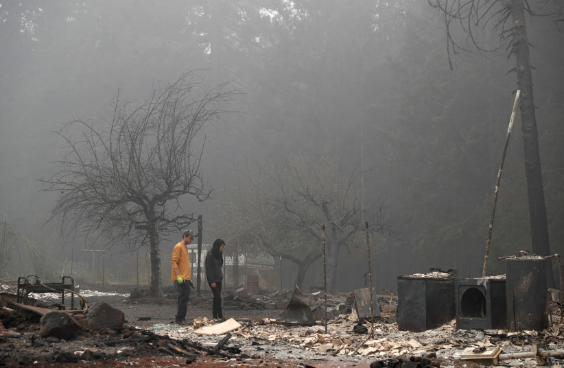 Dane Valentine, 28, and his wife Hansel, 24, inspect the remains of the burnt down property of their relatives, Estacada, Oregon, US, September 13, 2020  (photo credit: SHANNON STAPLETON / REUTERS)