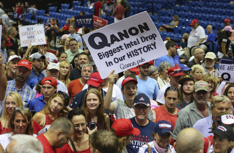 Trump supporters display QAnon posters at a 2018 rally in Florida. Recently, Latinos in the state have been inundated with anti-Semitic messages, many relating to the false QAnon conspiracy theory. (photo credit: THOMAS O'NEILL/NURPHOTO VIA GETTY IMAGES)